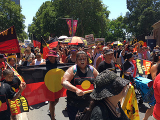 People carry Australian Aboriginal flags during a demonstration on Australia Day in Sydney