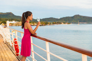 Wall Mural - Luxury cruise ship honeymoon vacation woman drinking wine during dinner at outdoor restaurant deck of sailing boat in Tahiti, French Polynesia. Elegant lady drinking wine on balcony watching sunset.