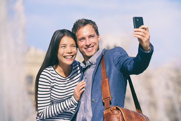Wall Mural - Selfie tourists couple taking photo with phone on sunny day in Europe trave city destination. Happy Asian woman, Caucasian man using mobile photo for holiday picture.