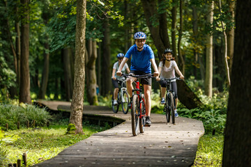 Healthy lifestyle - people riding bicycles in city park Wall mural