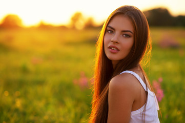 Beautiful sexy brunette girl is on nature over sunrise.