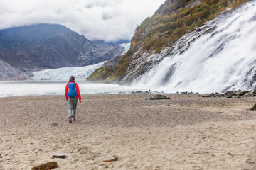 Mendenhall glacier in Juneau, Alaska. Woman tourist walking at famous attraction excursion on USA travel cruise.
