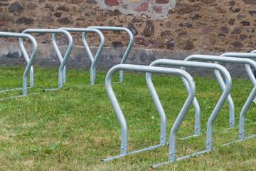 Leerer Fahrradständer auf Rasenfläche vor Event-Location