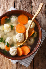Danish soup with double dumplings and vegetables close-up in a bowl. Vertical top view