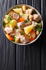 German stew Pihelsteiner with vegetables and three kinds of meat close-up in a bowl. Vertical top view