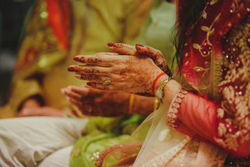 woman's hands decorated with henna at a hindu wedding