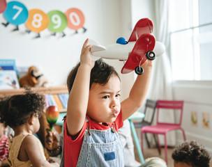 Obraz Preschooler enjoying playing with his airplane toy - fototapety do salonu