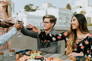 Happy friends toasting at a rooftop party