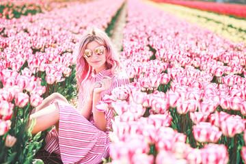 Smiling girl sitting in Tulip field