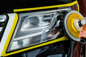 Car headlights with power buffer machine at service station - a series of CAR CARE
