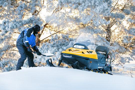 Man With Stuck Snowmobile. Sunrise, sunset winter day. Winter fun for man.