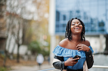 Attractive african american woman with dreads in jacket posed near railings against modern multistory building with mobile phone.
