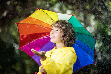Happy child playing in the rain