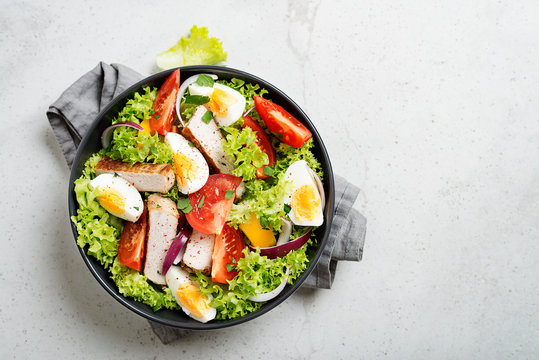 Fresh vegetable salad with chicken breast and eggs.