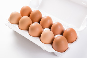 ten brown eggs in white package side view close-up