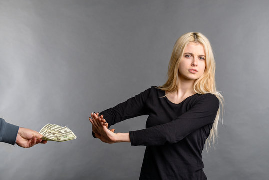 pretty blonde girl rejects money dollars banknotes woman does not take money, refusing accept bribe money