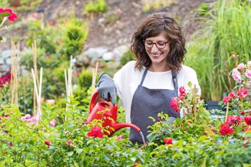 Freundlich lächelnde Gärtnerin beim bewässern der Rosen
