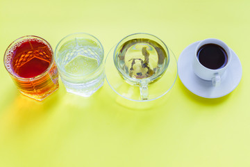 Top view of different beverages - drinking coffe, sparkling water, apple juice and green tea on yellow backgeound. Healthy life and diet concept