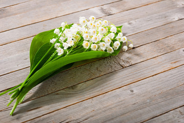 bouquet of lily of the valley on old weathered wooden table background