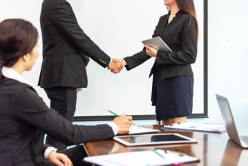 Two business people shaking hands conference training in meeting room ,finishing up a meeting.Business partners handshake while success job and project,greeting business deal,learning coaching concept