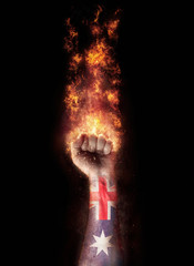 Australia flag in a hand which is on a fire