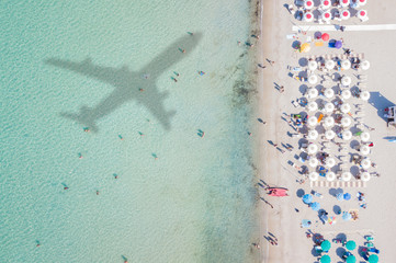 View from above, aerial view of an amazing white beach with a shadow of an airplane and people who swim on a transparent and turquoise  water.