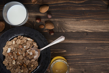 Flat lay of healthy breakfast with nuts and corn flakes on brown rustic background 6