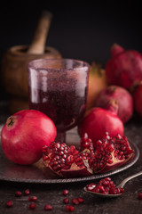 Pomegranate juice in a glass on the silver tray with fresh pomegranates around with scattered seeds on dark background