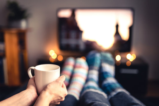 Couple drinking tea, hot chocolate, eggnog or mulled wine and watching tv in warm cozy woolen socks in winter. Woman holding cup of morning coffee in home living room. Sick people with flu or fever.