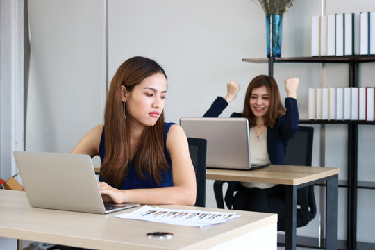 Young angry envious Asian business woman looking successful competitor colleague in office.