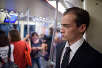 Young businessman traveling with underground train while thinking
