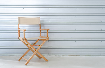 Modern folding fabric wooden movie director chair .Foldable chair on metal wall background interior design furniture living room concept, clipping path