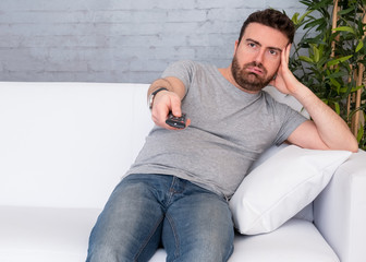 Man watching tv seated on the sofa at home