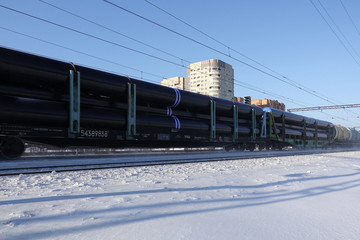The train carries large pipes for the pipeline. Winter. Snow from under the wheels. The effect of movement. Russia. Moscow region