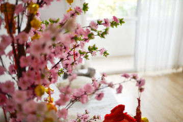 Cherry blossom, Sakura flowers, artificial flowers, fabric flowers in the modern room with windows full of light through white curtains