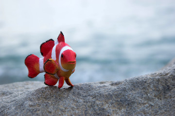 toy fish on a stone against the sea for text