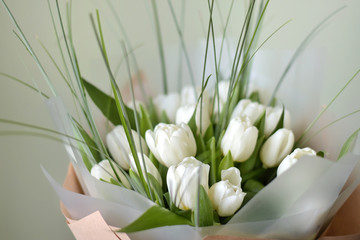 bouquet of white tulips on green background. Beautiful tender flowers with selective focus with long green leaves. Spring blossom for romantic valentines or mothers day. Fresh bunch of tulips.