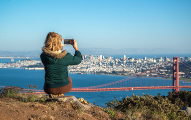 Young woman taking a photo with her phone of Golden Gate Bridge