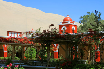 Foto op Canvas Zuid-Amerika land Red colored tower dome against the awesome sand dunes of Huacachina desert, the oasis town of Huacachina, Ica region, Peru