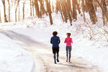Caucasian sporty friends dressed in sportswear running on the snow inn the morning with backs turned. Wintertime, healthy lifestyle concept.