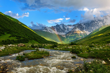 Rainbow over the rapid river and the snow-capped mountains. Georgia