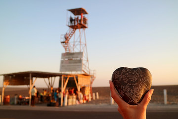 Foto op Canvas Zuid-Amerika land Woman's hand holding a souvenir of Nazca lines carved heart shaped stone against blurry observation tower of Nazca, Ica region, Peru, South America