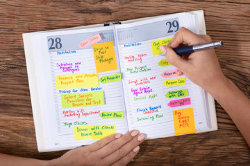 Fototapete - Businesswoman Writing Schedule In Diary With Pen