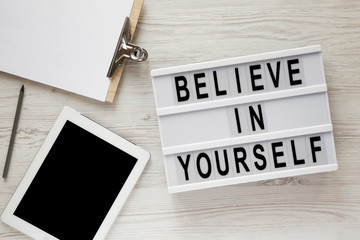 Modern board with text 'Believe in yourself', tablet, clipboard and sheet of paper on a white wooden surface, top view. Overhead.