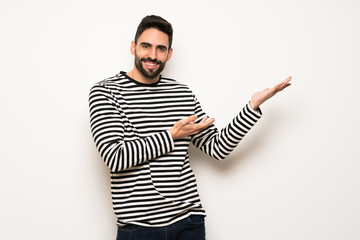 handsome man with striped shirt extending hands to the side for inviting to come