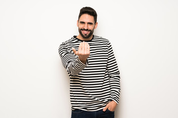 handsome man with striped shirt inviting to come with hand. Happy that you came