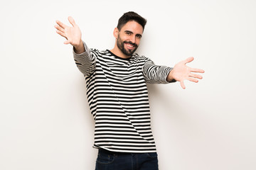 handsome man with striped shirt presenting and inviting to come with hand