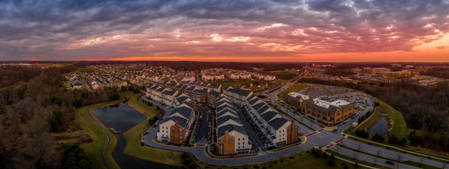 Aerial sunset panorama view of typical East Coast USA newly constructed suburban luxury townhouse community real estate in Maryland with brick facade the American Dream