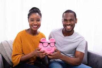 Couple Holding Pink Piggybank