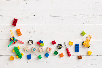 Multi-colored cubes of wood and plastic on a wooden background. Wooden cubes with the numbers of the year 2019. Toys and other equipment for the early development of the child.